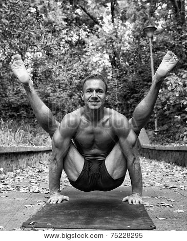 Athletic man doing yoga asanas in the park