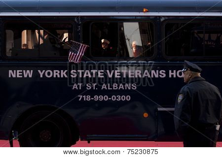 NEW YORK - NOV 11, 2013: An American Flag waves from the window of the NY State Veterans Home bus during the 2013 America's Parade held on Veterans Day in New York City on November 11, 2013.