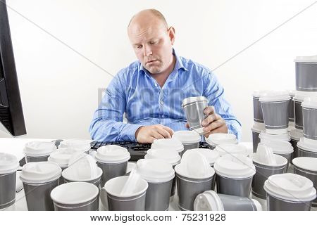 Overworked businessman drinking too much coffee