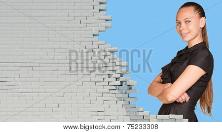 Beautiful businesswoman in dress smiling and looking at camera. Dilapidated brick wall as backdrop