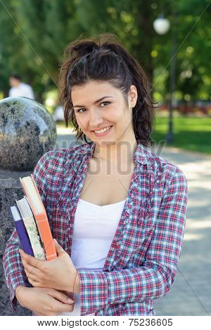 Girl Student Holding A Book In Her Hands.