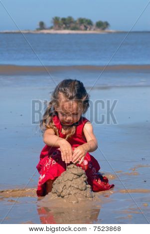 Girl On The Beach Playing With Sand
