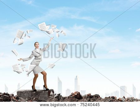 Young pretty businesswoman juggling with paper sheets