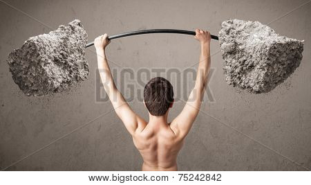 Funny skinny guy lifting large rock stone weights