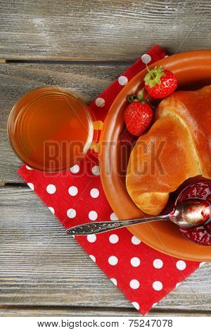 Breakfast with apple juice and  big fresh croissant on wooden background