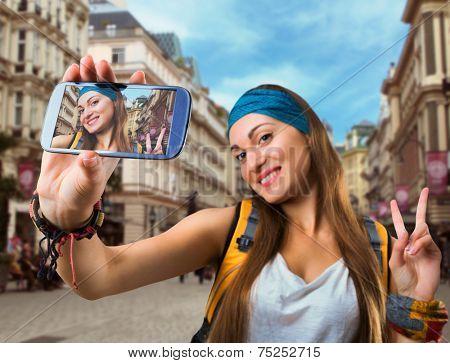 Happy traveler woman is taking selfie