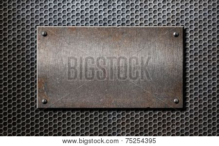 old rusty metal plate over grid or grille background