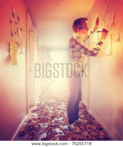 a girl writing on paper notes stuck to a wall in a bright hallway full of leaves that is backlit and toned with a retro vintage instagram filter effect