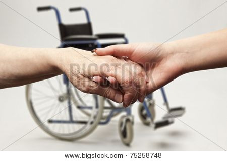 Hands of an elderly woman holding the hand of a younger woman on wheelchair background