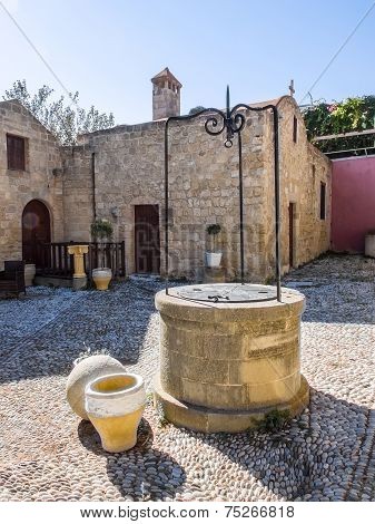 Courtyard And Well At Ancient Church. Rhodes. Greece