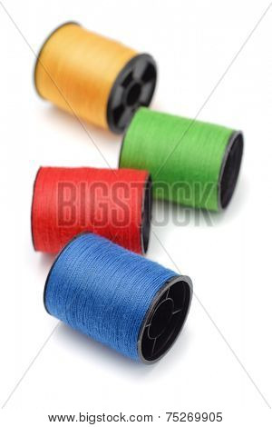 Four bobbins of color thread isolated on white