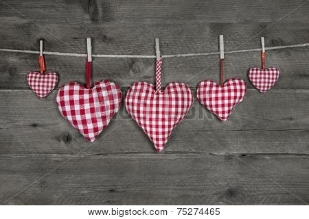 Five handmade red white checkered hearts hanging on a cord on wooden grey background.