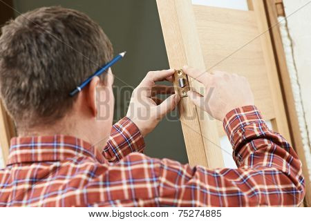 Male worker handyman carpenter at lock installation into wood door