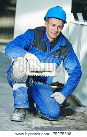 Portrait of industrial tiler builder worker installing floor tile at repair renovation work