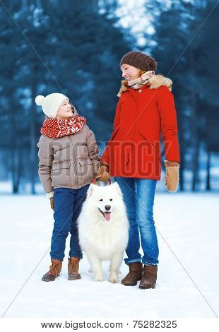 Christmas, Winter And People Concept - Beautiful Happy Family Having Fun, Mother And Son Walking Wit