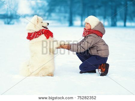 Christmas, Winter And People Concept - Happy Teenager Boy Playing With White Samoyed Dog Outdoors In