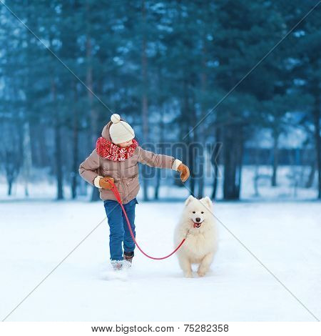 Christmas, Winter And People Concept - Happy Teenager Boy Running And Playing With White Samoyed Dog