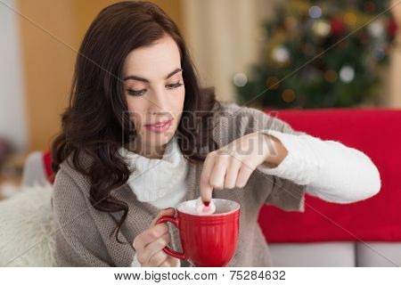 Brunette dunking marshmallow in hot chocolate at christmas at home in the living room
