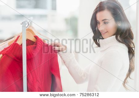 Pretty brunette looking at clothes on rail at clothes store