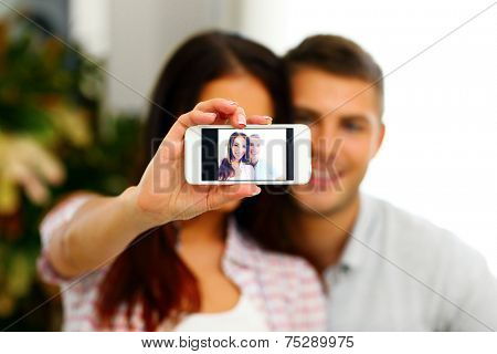 Portrait of a happy couple making selfie photo with smartphone. Focus on smartphone