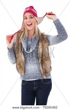 Blonde in winter clothes smiling at camera on white background