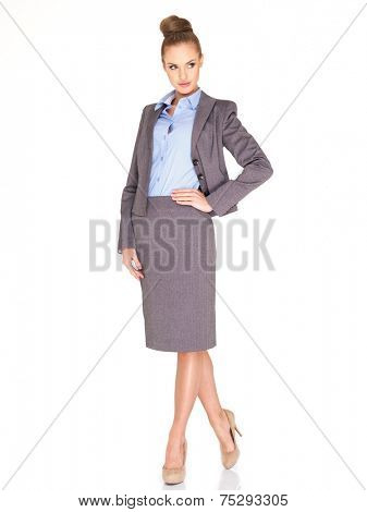 Elegant sophisticated professional woman in a stylish grey suit posing with her hand on her hip looking to the side  isolated on white