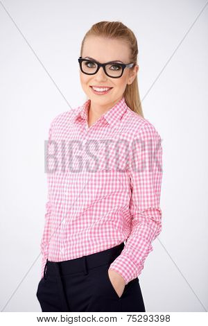Confident relaxed woman in glasses and a red checked shirt standing with her hands in her pocket smiling at the camera  on white