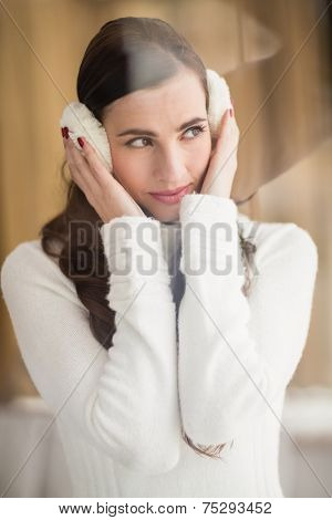 Pretty brunette with ear muffs thinking at home