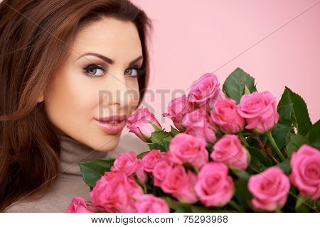 Gorgeous woman with a large bunch of fresh pink roses given her by a loved one for valentines  her birthday or anniversary