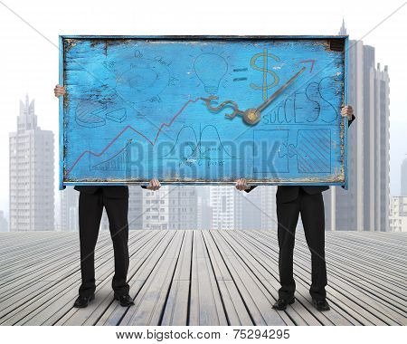 Two Men Holding Old Blue Doodles Billboard On Skyscraper Cityscape