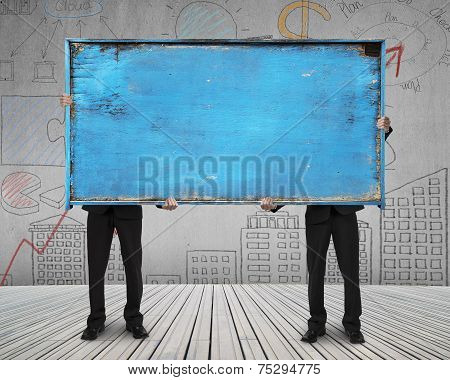 Two Businessman Hold Old Blue Blank Wooden Noticeboard Stand