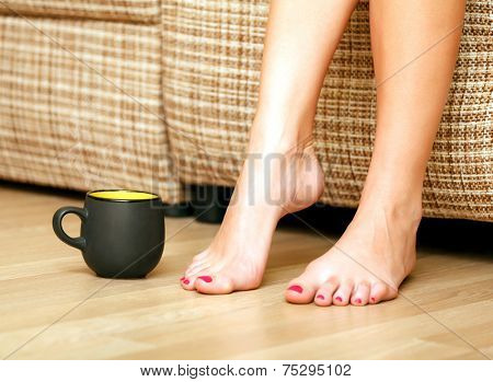 Female feet and a cup of tea or coffee