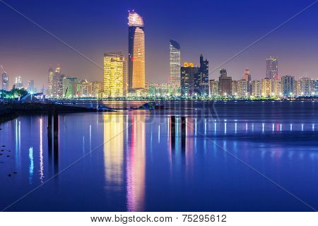 ABU DHABI, UAE - MARCH 28, 2014: Skyscrapers of Abu Dhabi at nightwith reflection in Persian Gulf, UAE. Abu Dhabi is the capital and the second most populous city of the United Arab Emirates
