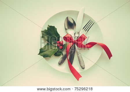 Holiday place setting, with red ribbon and holly berries covered in snow. Old retro vintage style.
