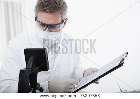 Doctor Working With Clipboard And Blood