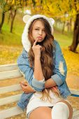 foto of debonair  - Pretty girl in a knitted bear hat posing in autumn park - JPG