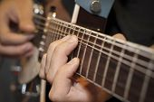 stock photo of fret  - close up shot of a man with his fingers on the frets of a guitar playing - JPG