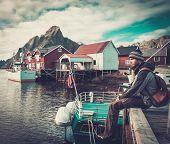 foto of reining  - Man traveller sitting on a pier in Reine village - JPG