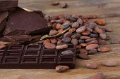 stock photo of cocoa beans  - Cracked chocolate bar and cocoa beans on wooden background - JPG