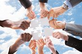 stock photo of jigsaw  - Directly below shot of multiethnic business people assembling jigsaw puzzle against sky - JPG