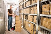 stock photo of hand truck  - Portrait of delivery man with stacked cardboard boxes on hand truck at warehouse - JPG