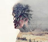 picture of toned  -  a serious looking woman side profile toned with vintage tones for a retro look and a double exposure with a field and trees - JPG