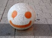 image of bollard  - bollard ball painted with smiling face on Alora pavement - JPG