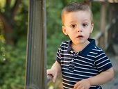 stock photo of fidget  - child holding on to a railing looking at camera - JPG