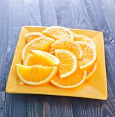 pic of valencia-orange  - fresh orange on the yellow plate and on a table - JPG