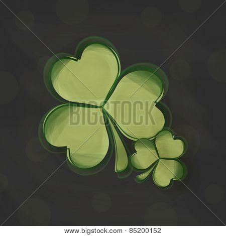 Irish lucky shamrock leaves on black background for Happy St. Patrick's Day celebration.