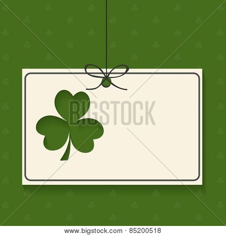 Blank hanging card with Irish lucky clover leaf on green background for Happy St. Patrick's Day celebration.