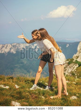 Two girls on mountain top looking landscape