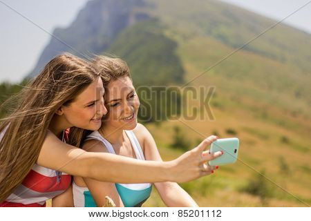 Girl on mountain with mobile phone taking self-ie