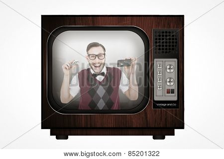 Geeky hipster holding a retro tape cassette player against retro tv